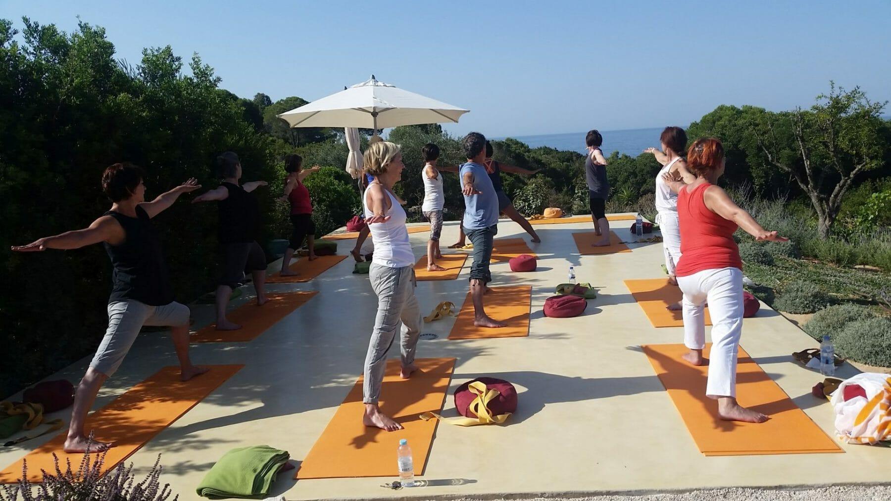 Yoga Retreat - Gruppe auf Yogaplattform im Sommer mit Blick aufs Meer
