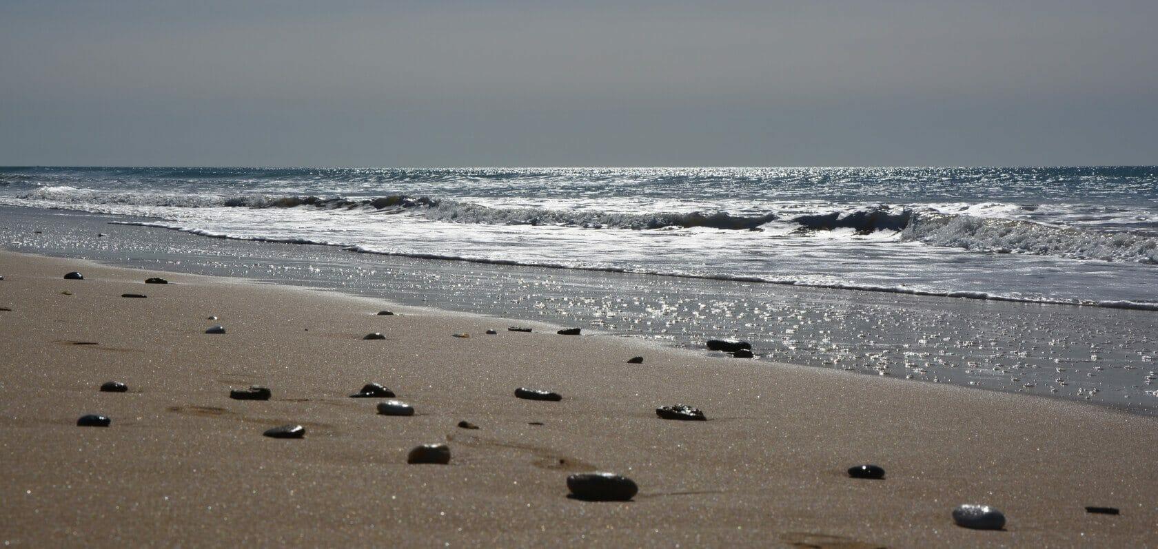 Qi Gong Urlaub am Meer - Steine auf Sandstrand am Meer