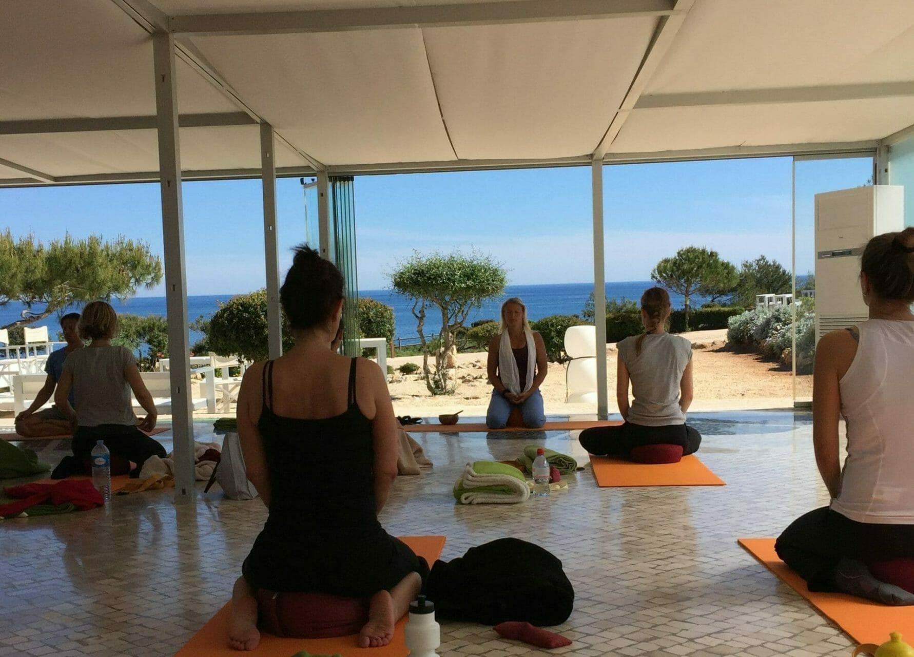 Gruppe in Meditation bei Yoga Urlaub am Meer