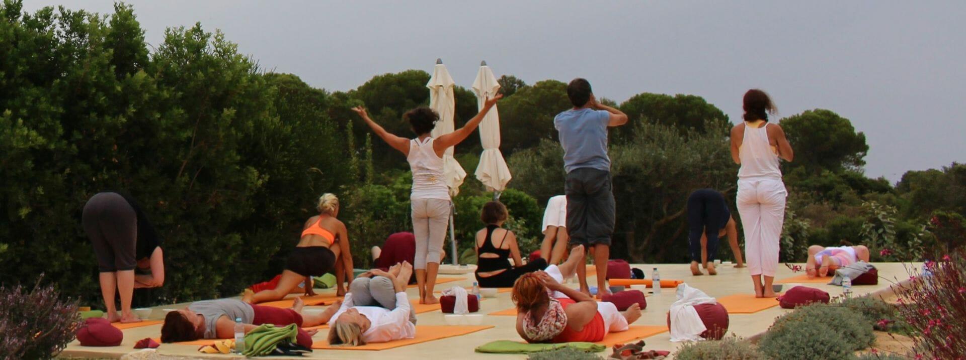 Yoga Retreat Gruppe praktiziert Sonnengrüße